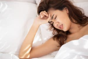 stressed woman with grinding teeth, bruxism symptoms; portrait of stressful, exhausted, tired sleeping woman grinding teeth on bed; oral wellness, dental care medical concept