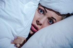 scared woman hiding behind blanket and looking at camera in bedroom at home