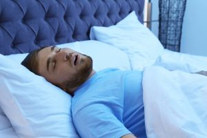 Young man snoring while sleeping in bed at night. Sleep disorder