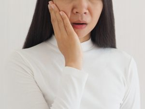 trigeminal neuralgia and temporomandibular joint and muscle disorder in asian woman, She use hand touching her cheek and symptoms fo pain and suffering on isoleted white background.